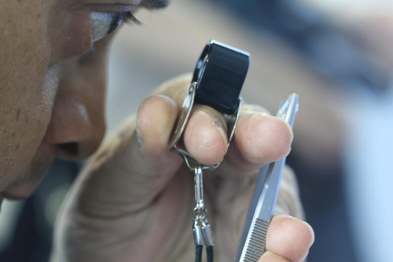 Suresh hathiramani inspecting a diamond through a 10x loupe | Facets Singapore